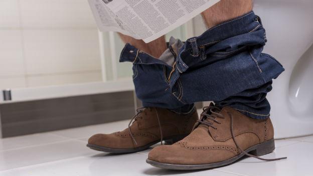 Mann sitzt auf der Toilette und liest Zeitung.