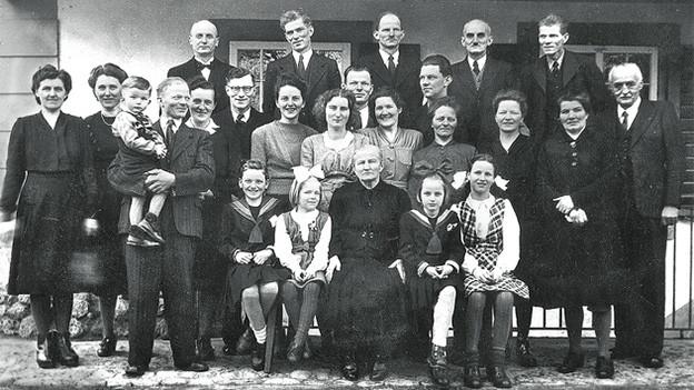 Schwarz-Weiss-Fotografie mit einem Gruppenbild einer Grossfamilie.