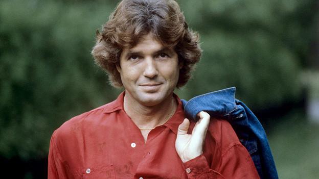 Ein Mann mit lockigen Haaren, rotem Hemd und über die Schulter geworfene Jeansjacke.