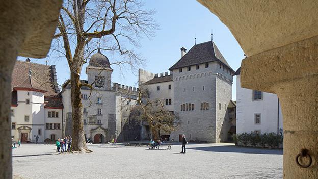 Blick auf einen Schlosshof, auf dem ein paar wenige Menschen spazieren.