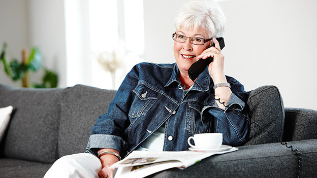 Eine lachende grauhaarige Frau mit dunkler Jeansjacke sitzt auf einem hellen Sofa und telefoniert.