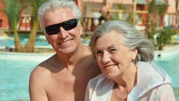 Ein älteres Paar am Pool. Er trägt eine Sonnenbrille, sie nicht.