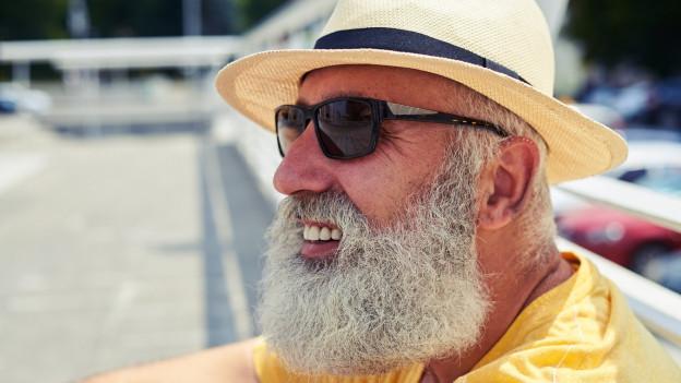 Mann mit Sonnenbrille und Sonnenhut.