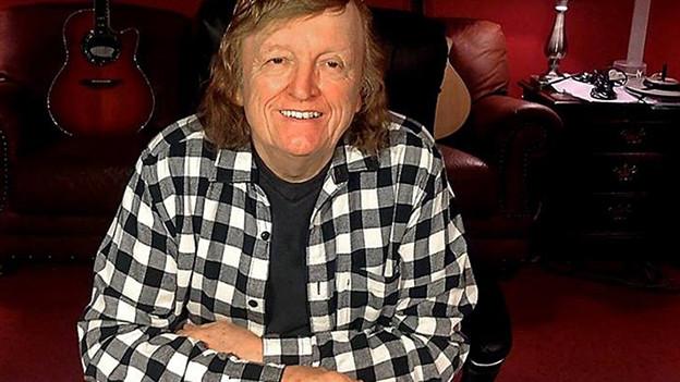 Ein Mann mit langen blonden Haaren und einem karierten Hemd sitzt in einem Raum voller Instrumente.
