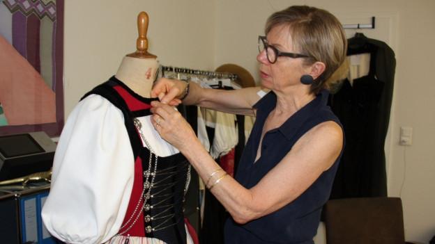 Malou Balmer näht an einer Tracht in ihrem Atelier.