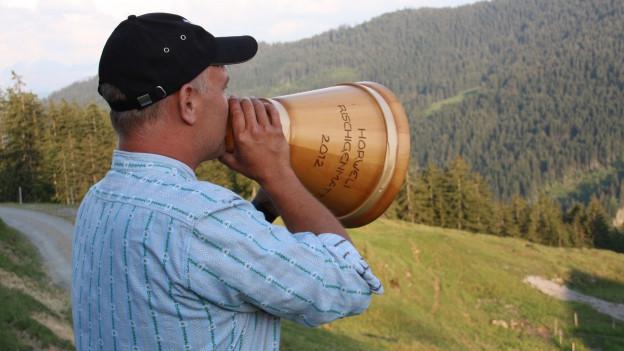 Armin Felix ruft mit dem Holztrichter in der Hand den Alpsegen