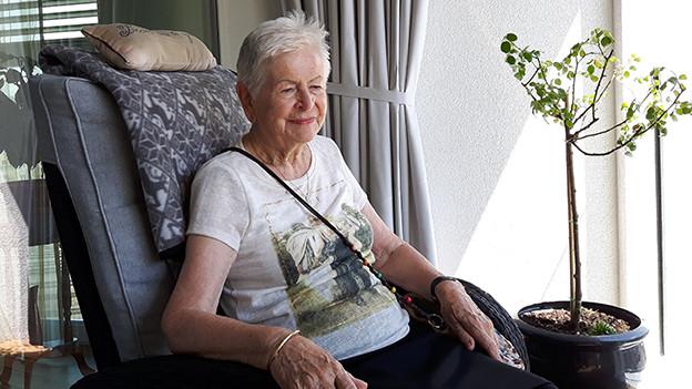 Eine ältere Frau mit grauen Haaren sitzt zufrieden in einem grossen Sessel.