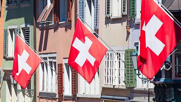 Mehrere Fahnen mit weissem Kreuz auf rotem Grund wehen an einer Häuserfassade.