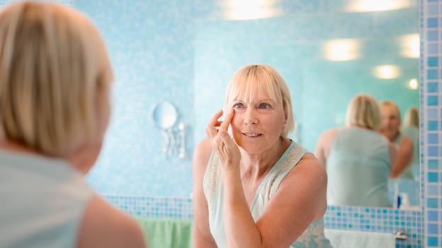 Frau schaut sich im Spiegel an und cremt ihr Gesicht ein.