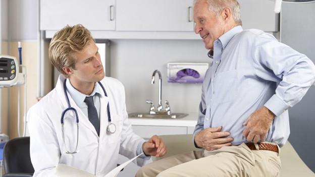 Ein Arzt behandelt die Hüfte eines älteren Mannes.