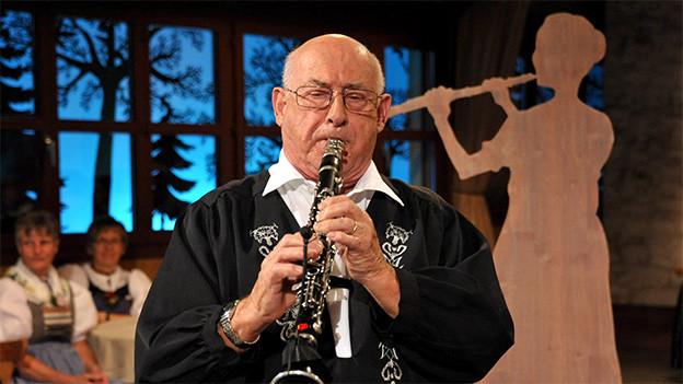 Ein Klarinettist in einem schwarzen Sennenhemd.