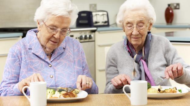 Zwei ältere Frauen beim Essen.