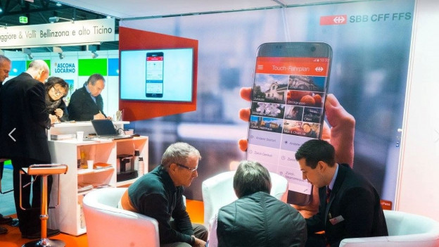Menschen mit Handy am Informationsstand.