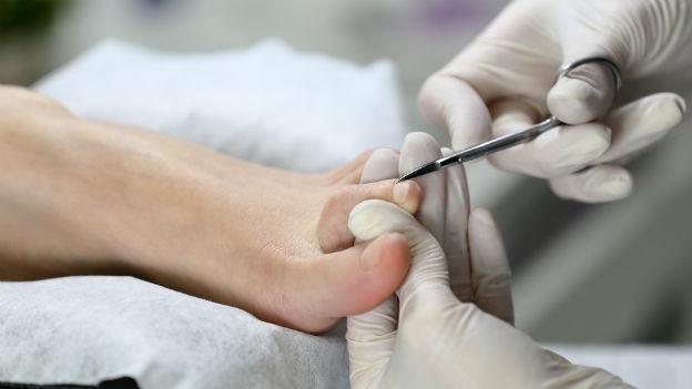 Podologin behandelt den Fuss einer Patientin.