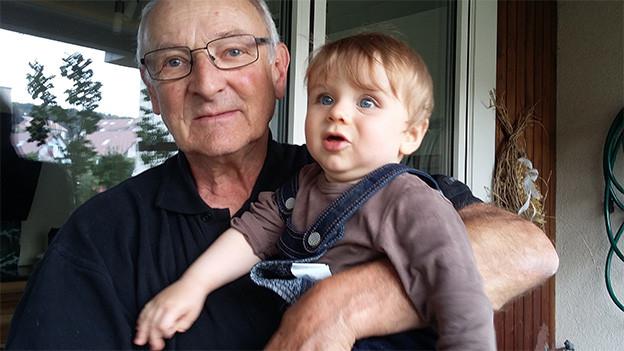 Ein älterer Mann mit einem Kleinkind auf dem Arm.