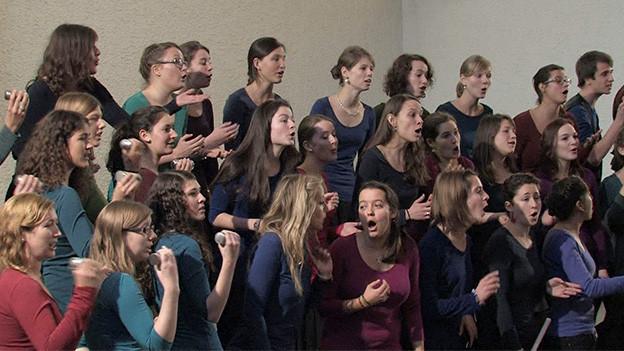 Eine Gruppe junger Männer und Frauen beim Singen.