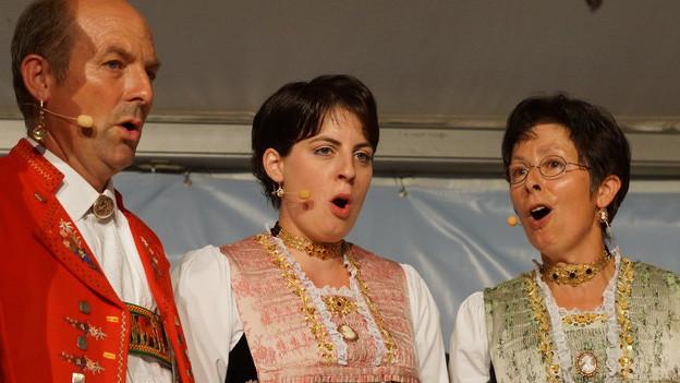 Ein Jodler und zwei Jodlerinnen in Appenzeller Trachten.