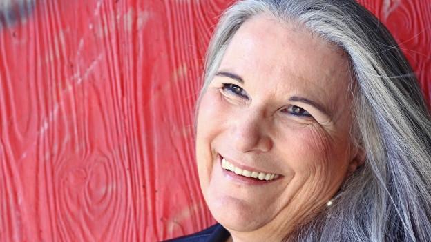 Frau mit langen grauen Haaren.