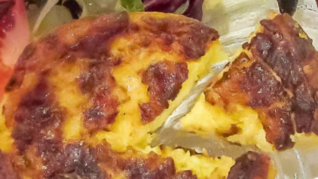 Stück Käsekuchen mit Salat.