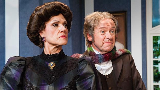 Szene aus einem Theaterstück mit einer ernst blickenden Frau und einem schmunzelnden Mann.