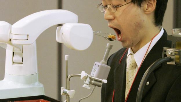 Roboter füttert Mann