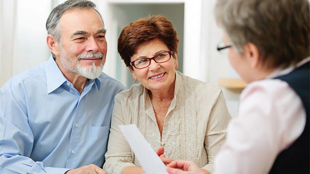Ein älteres Ehepaar im Gespräch mit einer Beraterin.