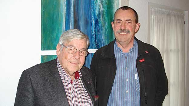 Zwei Männer vor einem blau-grünen Gemälde.