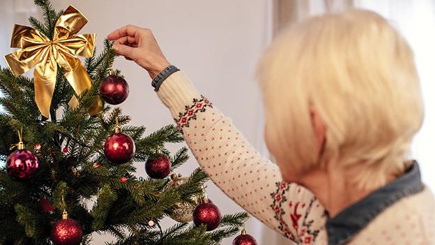 Eine ältere Frau schmückt einen Weihnachtsbaum.