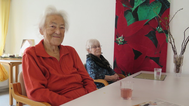 Zwei ältere Frauen an einem Esstisch.