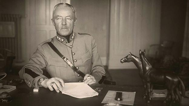 Ein Mann in Militäruniform sitzt hinter seinem Schreibtisch aus massivem Holz.