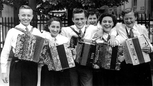 Gruppenbild mit fröhlichen jungen Menschen mit Handharmonikas.