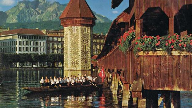 Eine Gruppe von Buben in einem kleinen Boot unterhalb einer Holzbrücke.