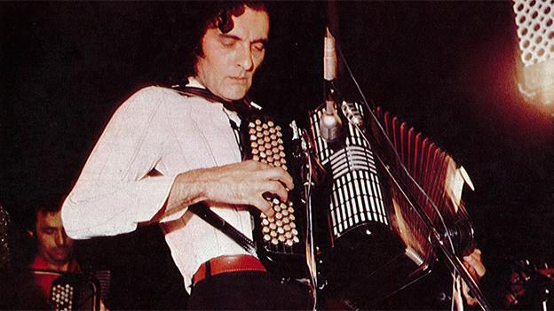 Ein Akkordeonist auf einer Konzertbühne.