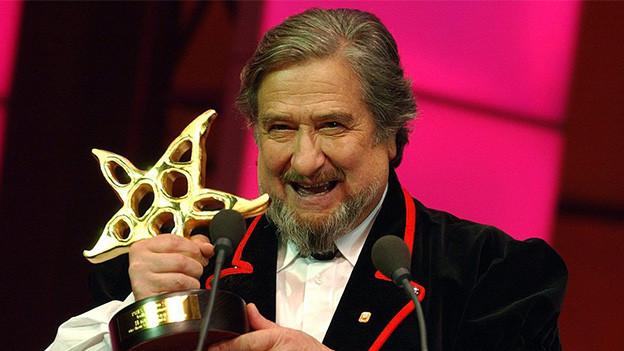 Ein Mann in einer Sennenkutte hält einen Auszeichnung in Form eines Sterns.