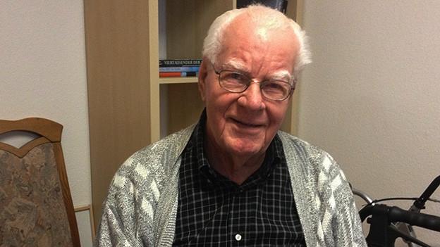 Ein älterer Mann mit Brille lacht in die Kamera.