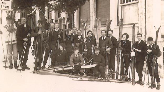 Schwarz-Weiss-Fotografie mit einer Gruppe von Skifahrerinnen und -fahrern mit historischer Ausrüstung.