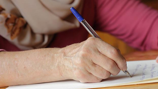 Hand einer Frau, die einen Brief schreibt.