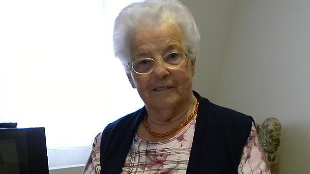 Porträt eine älteren Frau mit weissen Haaren, die vor dem Fenster ihres Wohnzimmers sitzt.