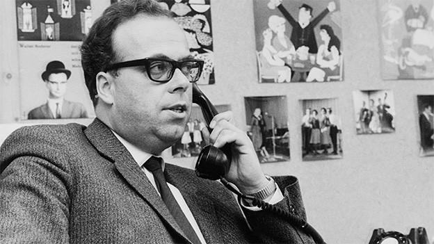 Die Schwarz-Weiss-Fotografie zeigt einen Mann, der in einem Büro telefoniert.