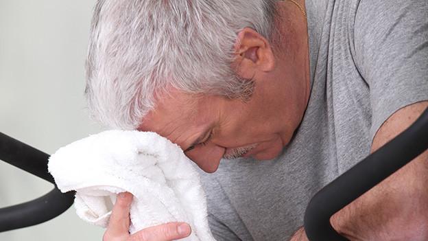Ein erschöpfter Mann wischt sich mit einem weissen Handtuch den Schweiss von der Stirn.