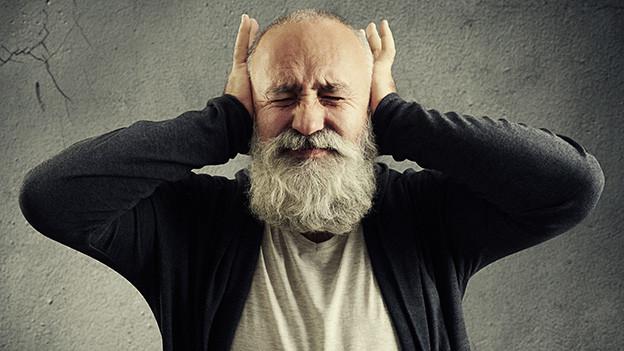 Ein alter Mann mit grauem Bart hält sich grimmig die Ohren zu.