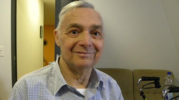 Ein älterer Mann trägt ein kariertes Hemd, hat einen wachen Blick und sitzt in einem Wohnzimmer.
