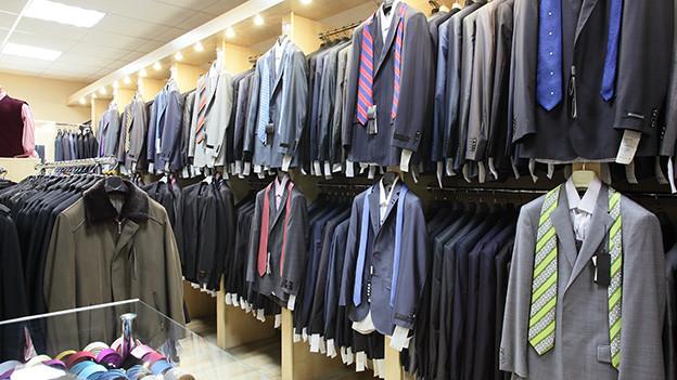 Anzüge und Krawatten in einem Geschäft für Herrenbekleidung.