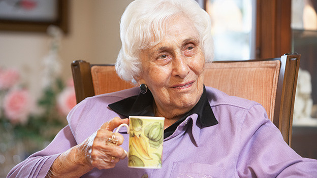 Eine alte Frau mit weissen Haaren sitzt mit einer Tasse Kaffee in einem Sessel.