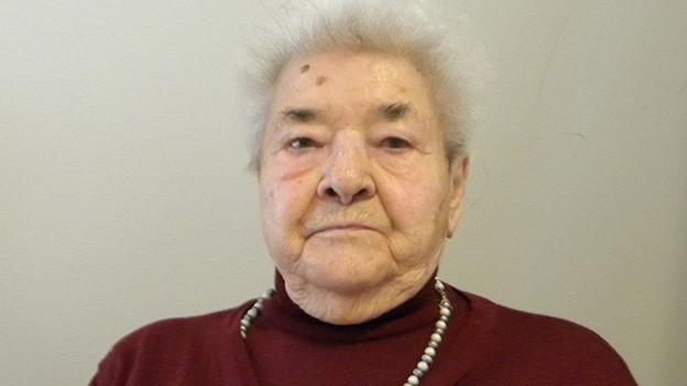 Eine ältere Frau mit grauen Haaren, weinrotem Pullover und Perlenkette.