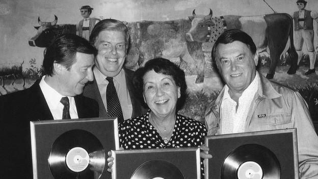 Zwei Männer und eine Frau zeigen lachend ihre Goldene Schallplatte.