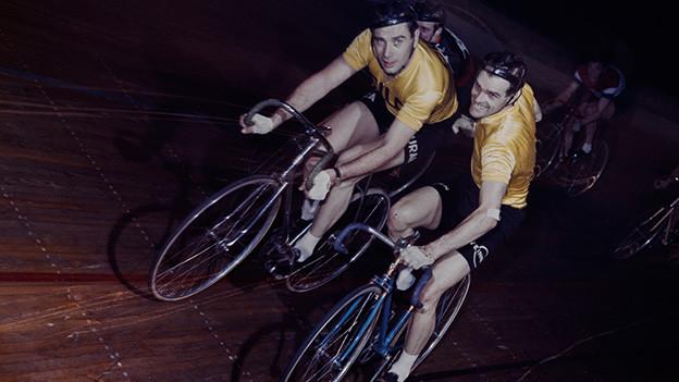 Zwei Radfahrer auf einer Rennbahn.