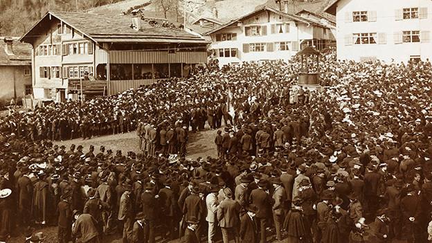 Historische Aufnahme von einem Dorfplatz, auf dem eine Menschenmenge versammelt ist.