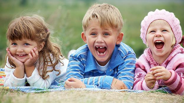 Zwei Mädchen und ein Bub liegen lachend im Gras.