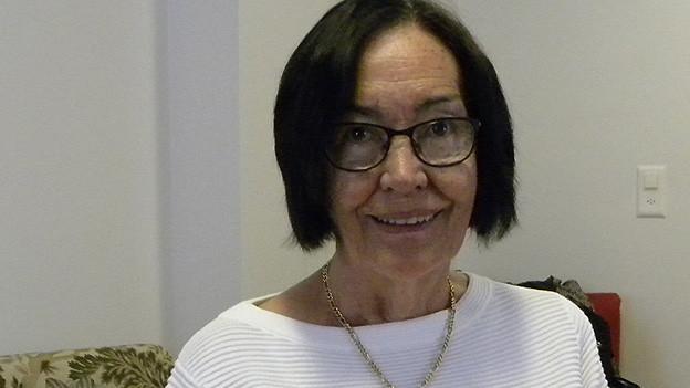 Porträt eine älteren Frau mit dunklen Haaren und Brille.